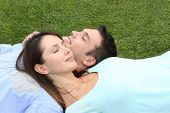 Top view of couple relaxing with eyes shut in grass