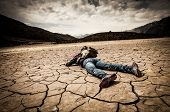 stock photo of deceased  - traveller lays on the dried ground - JPG