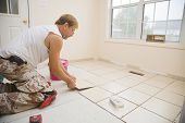 foto of grout  - Man installing ceramic tile in customers kitchen getting ready to sell home