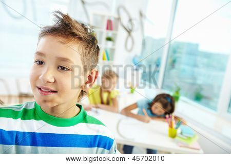 Portrait of handsome learner doing sums with schoolmates on background