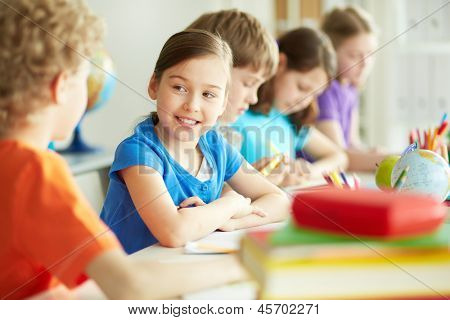 Portrait of happy diligent pupil looking at her classmate at lesson