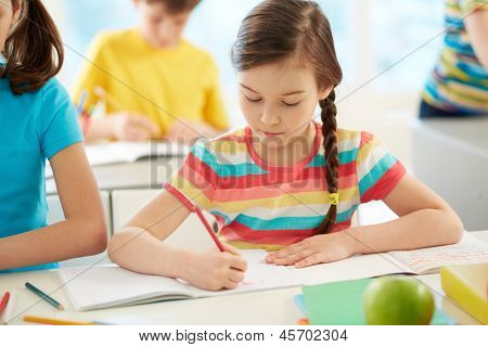 Portrait of lovely girl drawing at workplace surrounded by schoolmates