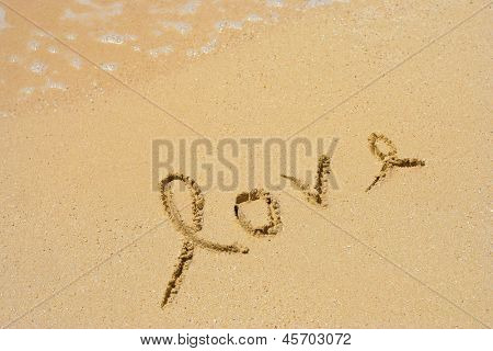 Concept or conceptual hand made or handwritten love text in sand on a beach in an exotic island
