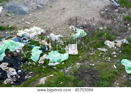 Concept or conceptual unhygienic polluted roadside,sewage or dirty road and grass with waste,trash and dump background