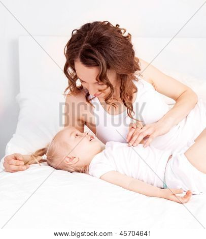 happy mother and her two year old daughter in bed at home