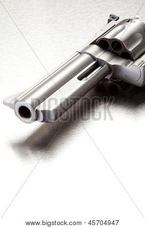 Gun on brushed metal surface - modern revolver with copyspace.