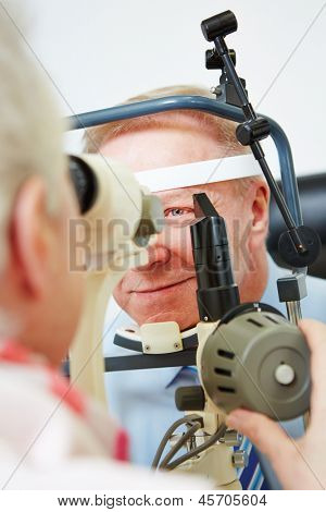 Oculist measuring cornea of elderly man with slit lamp
