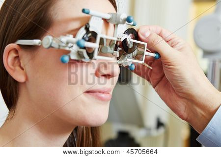 Optician determing prescription values with trial frame for a young woman
