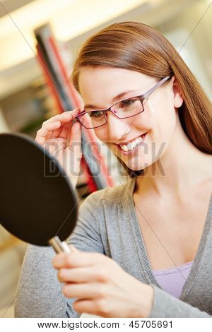 Happy smiling woman with new glasses looking in mirror at optician