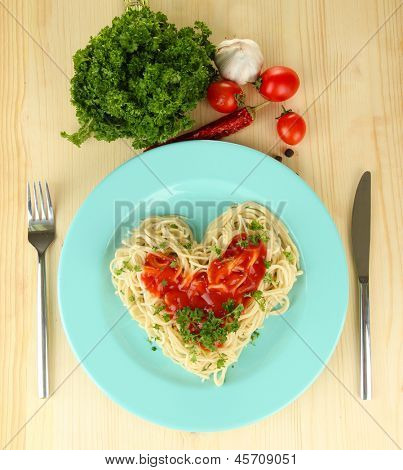 Cooked spaghetti carefully arranged in  heart shape and topped with tomato sauce, on  wooden background