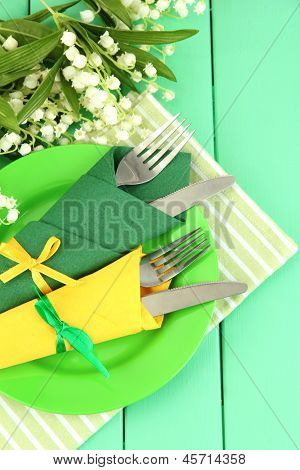 Forks and knives wrapped in green and yellow paper napkins, on color wooden background