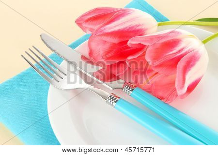 Festive dining table setting with tulips on beige background