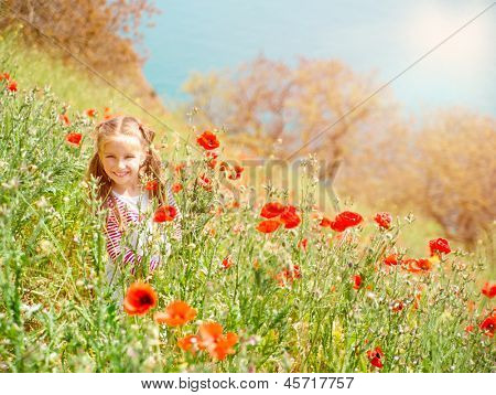 smiling little girl in a poppy field