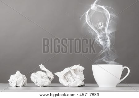 idea birth. crumpled wads and bulb silhouette on gray
