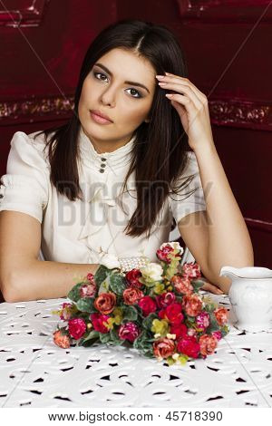Young beautiful pensive woman sitting at the table with flowers on it