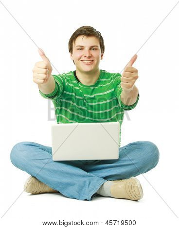Young man sitting on the floor with laptop and showing ok, isolated on white background