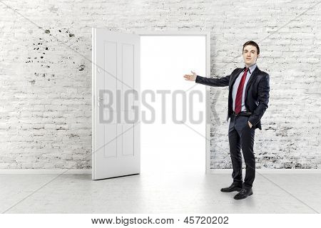 business man in front of an open door in a vintage white brick wall