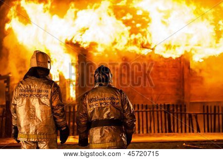 Arson or nature disaster - firefighters at burning fire flame on wooden house roof. Inscription on back says they are workers of fire prevention department of Russian rescue service.
