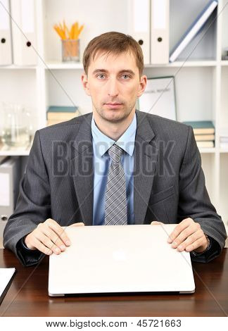 Young businessman with laptop computer shouting down on his workplace