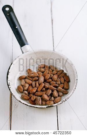 roasted cocoa chocolate beans in pan on white wood background