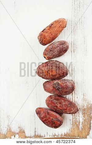 roasted cocoa chocolate beans on white wood background