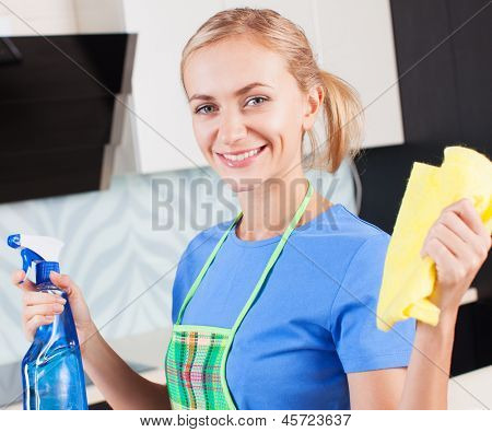 Woman cleaning kitchen. Young woman washing house