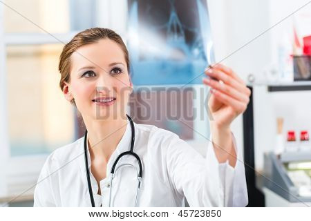 Radiology - female Doctor looking at a tomography x-ray picture of a skull