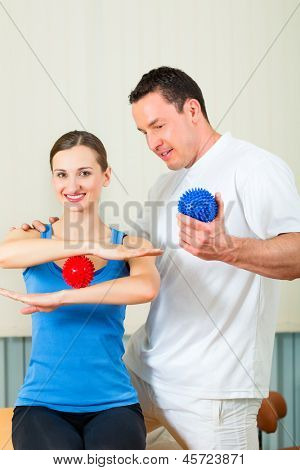 Female Patient at the physiotherapy doing physical exercises with her therapist, they using a massage ball