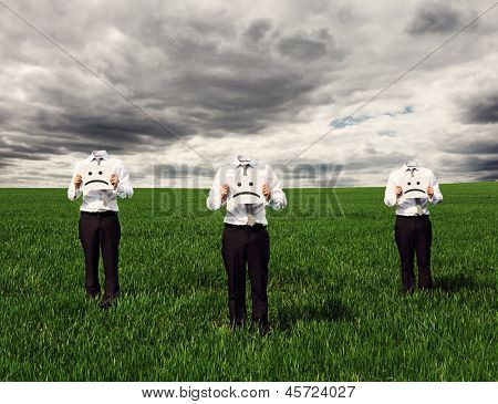 faceless businessmen holding placard with sad sing