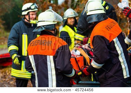 Accident - Fire brigade and Rescue team pulling cart with wounded person wearing a neck brace and respirator