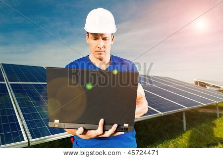 Photovoltaic system with solar panels for the production of renewable energy through solar energy, a technician standing in front with a laptop