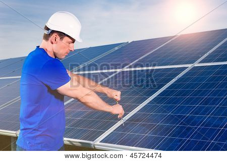 Photovoltaic system with solar panels for the production of renewable energy through solar energy, a technician using a screwdriver or tool