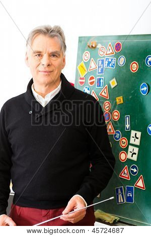 Driving school - driving instructor in his class, he standing in front of a blackboard and looking in the camera, in the background are traffic signs