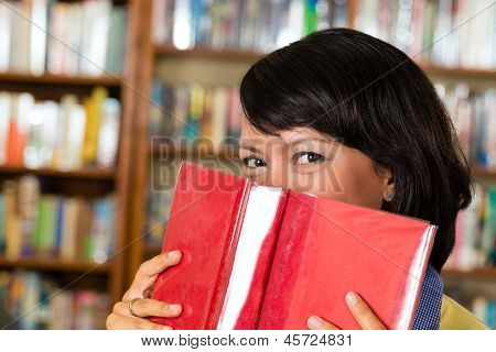 Student - young Asian woman or girl learning in library and reading, she hides behind a book