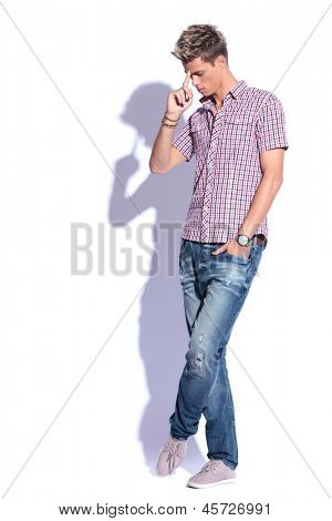 full length picture of a casual young man standing with a hand in his pocket and trying to remember something with a finger on his forehead and eyes closed. on white background with shadow