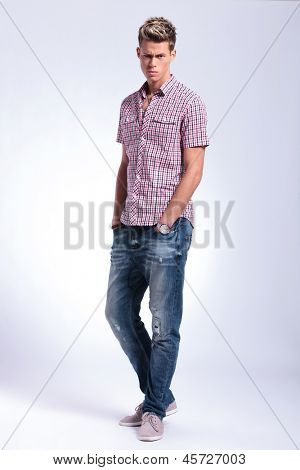 full length picture of a casual young man standing with his hands in his pockets and looking at the camera with a raised eyebrow. on gray background