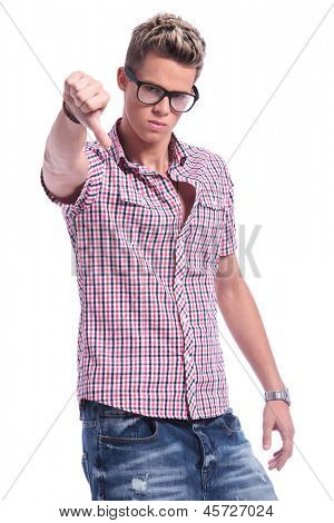 casual young man showing thumbs down gesture while looking at the camera with an angry face. on white background