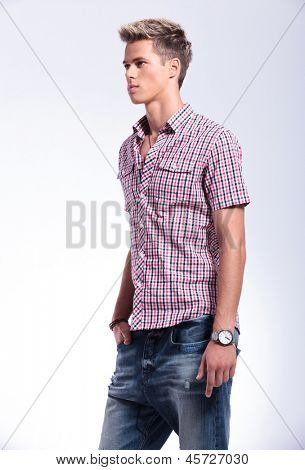 angle view of a casual young man standing with a hand in his pocket and looking away from the camera. on background