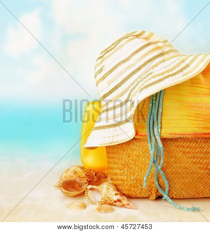 Beach accessories on the sand near sea, skin protection, seashell, hat, bag, day spa, tropical resort, luxury lifestyle,  summertime vacation