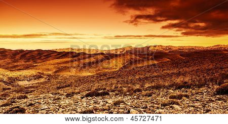 Photo of beautiful red dramatic sunset in desert, sandy mountains landscape, summer season, travel and tourism concept