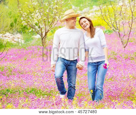 Young loving couple walk in spring park, first love, romantic date, springtime holidays, spending time together outdoors