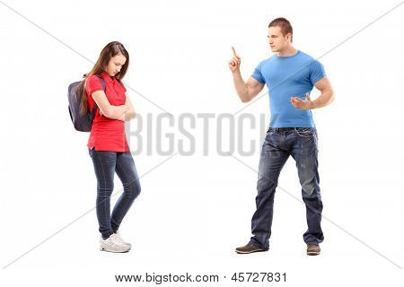 Full length portrait of an angry brother pointing with finger and threatening at his sister isolated on white background