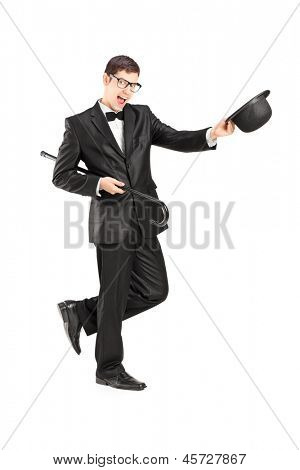 Full length portrait of cheerful young man in a bow tie suit and top hat isolated on white background