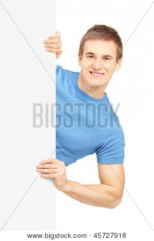 Casual young man posing behind white panel, isolated on white background