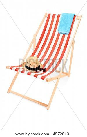 Studio shot of a sun lounger with towel, hat and sunglasses isolated on white background
