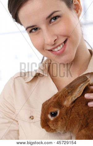 Portrait of happy woman smiling at camera, holding cute bunny pet.