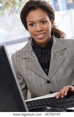 Young ethnic businesswoman sitting at desk, working with computer, smiling.