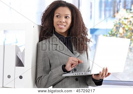 Portrait of beautiful afro-american businesswoman with laptop computer smiling, looking away.