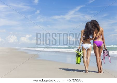 Rear view of two beautiful young women in bikinis with snorkel, mask & flippers embracing on a deserted beach with blue sky