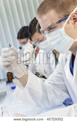 A male medical or scientific researcher or doctor looking at a test tube of clear liquid in a laboratory with female colleagues.